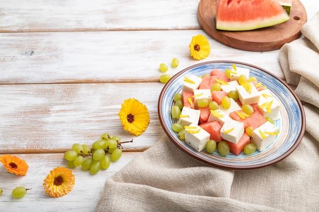 Vegetarischer salat mit wassermelone, feta-käse und trauben auf blauem keramikteller auf weißem holzhintergrund und leinentextil. seitenansicht, kopierraum.