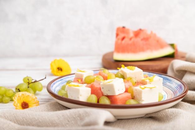 Vegetarischer salat mit wassermelone, feta-käse und trauben auf blauem keramikteller auf weißem holzhintergrund und leinentextil. seitenansicht, nahaufnahme, selektiver fokus.