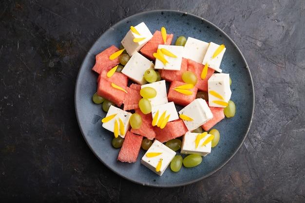 Vegetarischer salat mit wassermelone, feta-käse und trauben auf blauer keramikplatte auf schwarzem betonhintergrund. draufsicht, nahaufnahme, flach liegen.