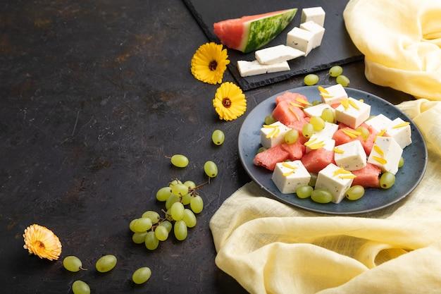 Vegetarischer salat mit wassermelone, feta-käse und trauben auf blauer keramikplatte auf schwarzem betonhintergrund und gelbem leinentextil. seitenansicht, kopierraum.