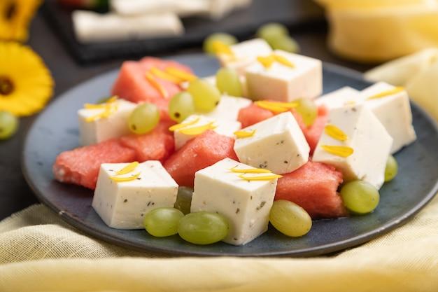 Vegetarischer salat mit wassermelone, feta-käse und trauben auf blauer keramikplatte auf schwarzem betonhintergrund und gelbem leinentextil. seitenansicht, nahaufnahme, selektiver fokus.