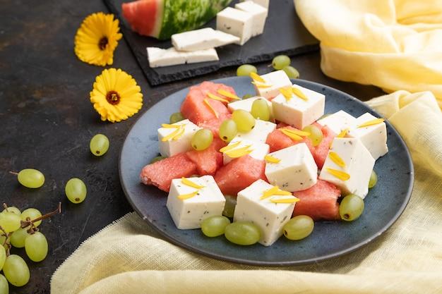 Vegetarischer salat mit wassermelone, feta-käse und trauben auf blauer keramikplatte auf schwarzem betonhintergrund und gelbem leinentextil. seitenansicht, nahaufnahme.