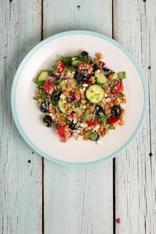 Vegetarischer salat quinoa, tomaten, gurken, kichererbsen, oliven, kräuter, hüttenkäse