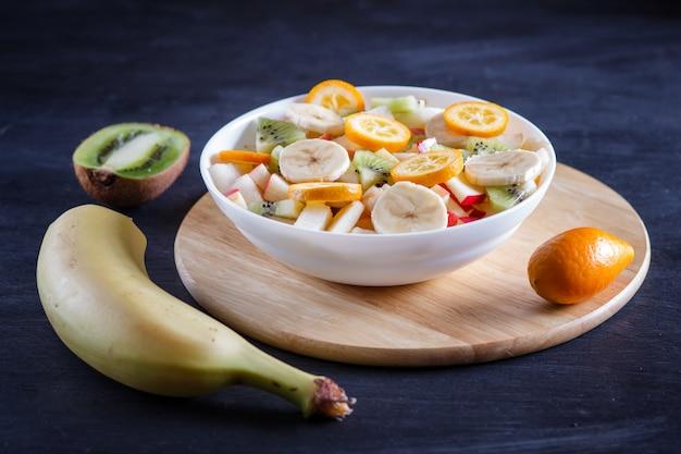 Vegetarischer salat von bananen, von äpfeln, von birnen, von japanischen orangen und von kiwi auf schwarzem hölzernem hintergrund.