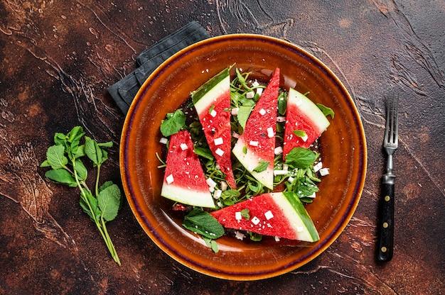 Vegetarischer wassermelonensalat mit fetakäse, rucola, zwiebeln. dunkler hintergrund. ansicht von oben.