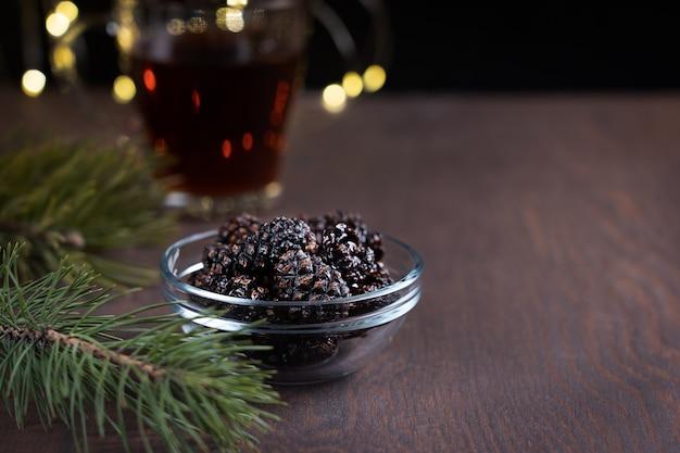 Vegetarisches dessert von getrockneten tannenzapfen in der schüssel auf dunklem holztisch mit tasse tee