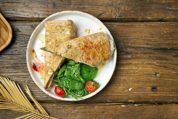 Vegetarisches dönerbrötchen mit spinat, tomaten, hummus und geschmolzenem käse in einem teller auf einem holz