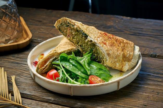 Vegetarisches dönerbrötchen mit spinat, tomaten, hummus und geschmolzenem käse in einem teller auf einem holztisch