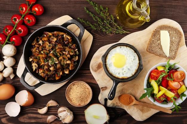 Vegetarisches essen. gebratene champignons und ei in gusseisenpfanne. bestandteile zum rustikales frühstück auf holztisch.