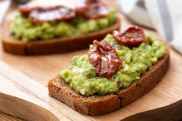 Vegetarisches essen. roggenbrot mit guakomole, avocadoteigwaren und getrockneten tomaten, auf hölzernem schneidebrett. avocado toast.