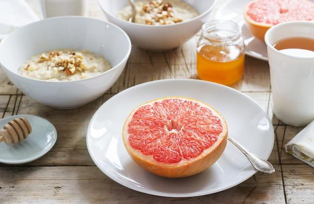 Vegetarisches frühstück für zwei haferflocken, gebackene grapefruit und tee. rustikaler stil.