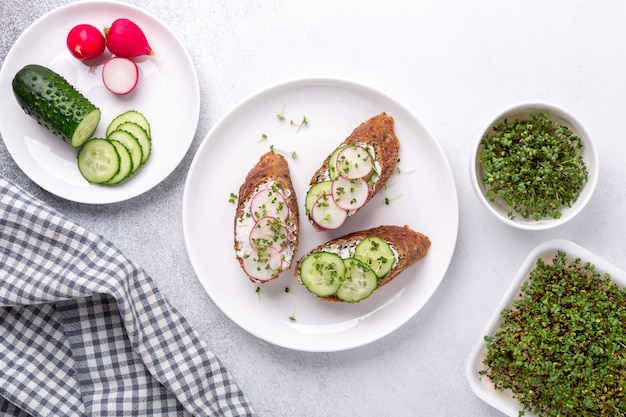 Vegetarisches frühstück. getreidebrot mit frischkäse, gurke, radieschen und senf-mikrogrün. mikrogrün in der schüssel. draufsicht. gesunder snack