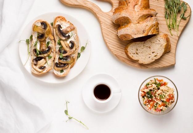 Vegetarisches frühstück ohne fleischprodukte. auf einem weißen tisch kaffee, ein salat aus bulgur tabule, pilze sandwiches.