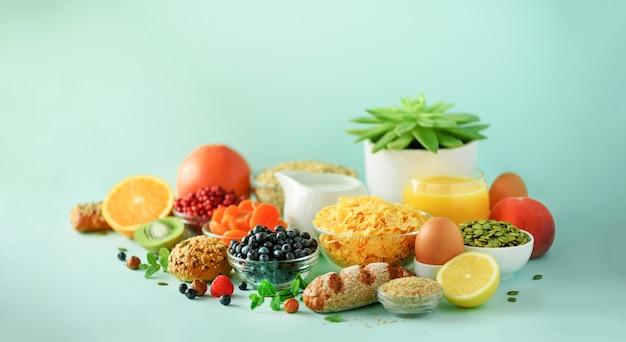 Vegetarisches frühstück. weiches gekochtes ei, haferflocken, nüsse, früchte, beeren, milch, joghurt, orange, banane, pfirsich auf blauem hintergrund. gesunde ernährung.
