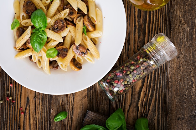 Vegetarisches gemüseteigwaren penne mit pilzen in der weißen schüssel auf holztisch. veganes essen. ansicht von oben