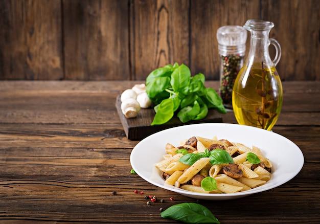 Vegetarisches gemüseteigwaren penne mit pilzen in der weißen schüssel auf holztisch. veganes essen. Kostenlose Fotos