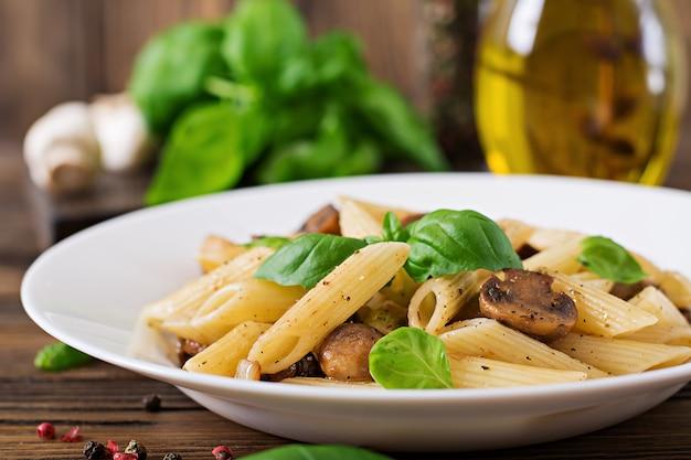 Vegetarisches gemüseteigwaren penne mit pilzen in der weißen schüssel auf holztisch. veganes essen.