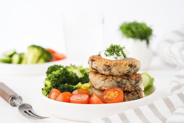 Vegetarisches gericht von kartoffelpastetchen mit kräutern und gemüse auf einem teller