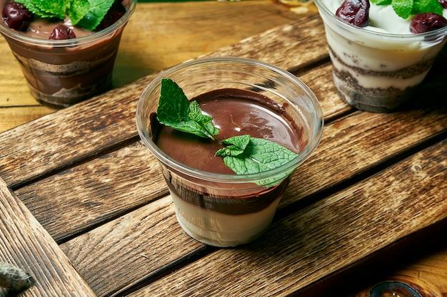 Vegetarisches gesundes dessert kleinigkeit mit und weißer pudding schokolade und kirsche in einem plastikbehälter auf einem holztisch