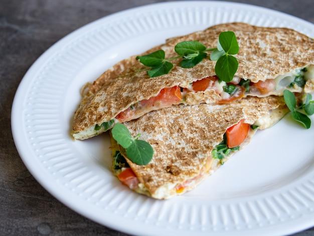 Vegetarisches gesundes frühstück von geschmolzenem dünnem pittabrot, käse, tomate und kräutern