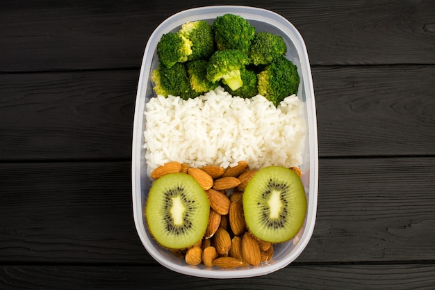 Vegetarisches mittagessen in der box auf der schwarzen holzoberfläche