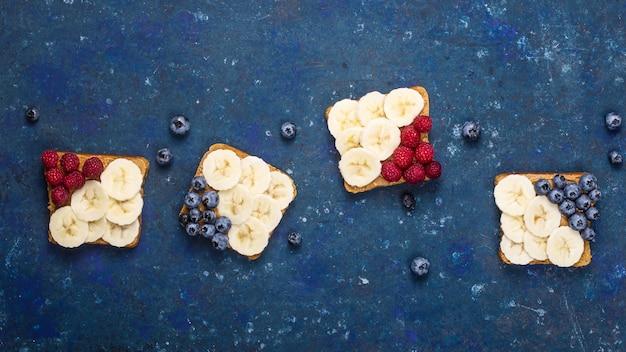 Vegetarisches mittagessen-sandwich mit erdnussbutter, banane, himbeere und blaubeere
