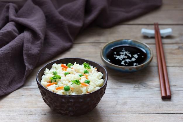 Vegetarisches reisgericht mit gemüse und erbsen auf einer holzoberfläche