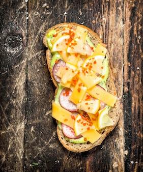 Vegetarisches sandwich mit käse, radieschen und frischer kräutersauce auf holztisch.