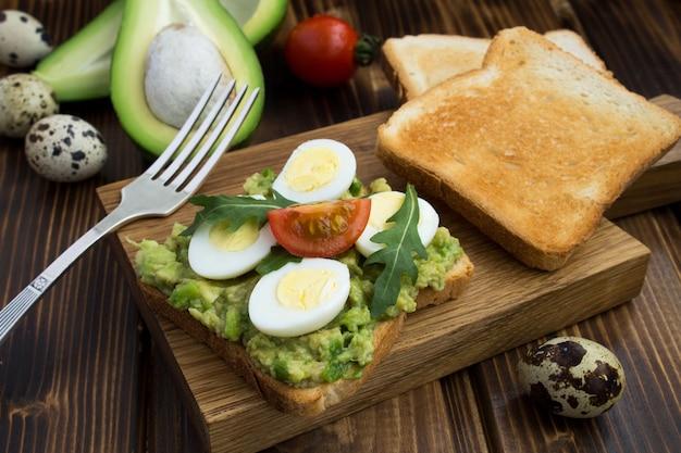 Vegetarisches sandwich mit wachteleiern, avocado und kirsche auf dem hölzernen schneidebrett