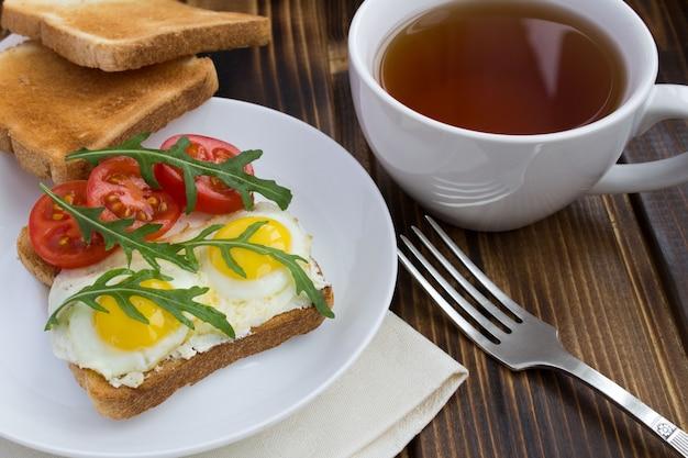 Vegetarisches sandwich mit wachteleiern, kirsche, rucola und tee auf dem hölzernen hintergrund