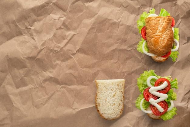 Vegetarisches sandwich-mockup-brot mit zwiebeln, tomaten und weißer mayonnaise-sauce latucce