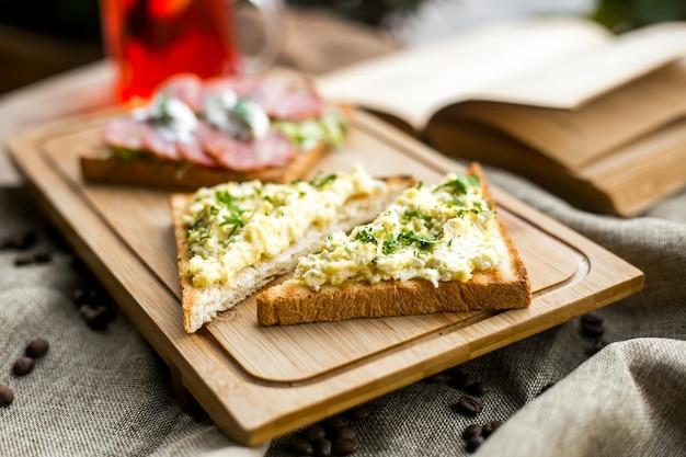 Vegetarisches sandwich-toastbrot-kartoffelpüree auf der seitenansicht des holzbretts