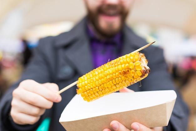 Vegetarisches und essenskonzept - gut aussehender mann, der beim fast-food-festival streetfood-mais isst