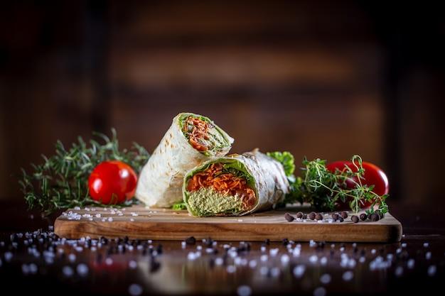 Vegetarisches wrap-sandwich auf hölzernem hintergrund