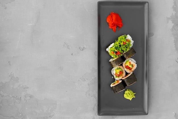 Vegeterianische sushirolle mit gemüse auf grauem hintergrund