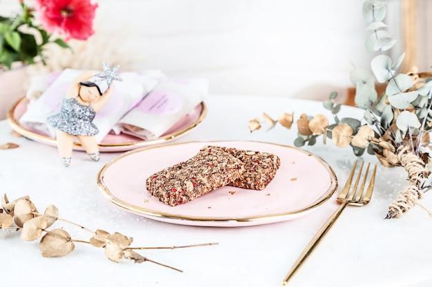Veggie gesunde riegel mit feigen serviert auf rosenteller über weißem hintergrund. schließen sie oben horizontales lebensmittelfoto. glutenfreies, gesundes dessert. veganes essen und süßigkeiten. hausgemachter snack. speicherplatz kopieren