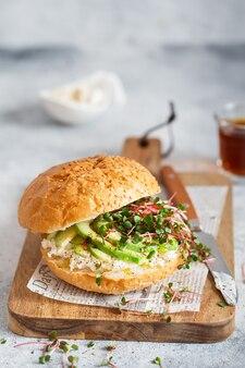 Veggie gesunder burger mit brot, frischer avocado und käse, garniert mit radieschen-microgreens