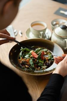 Veggie mädchen isst einen gesunden gemüsegemüsesalat mit basilikum, karotten und nüssen, garniert mit frischen erdbeeren. flache schärfentiefe, unscharfer hintergrund