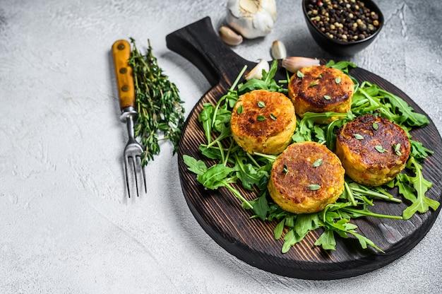 Veggie-pastetchen-schnitzel mit linsen, gemüse und rucola. weißer hintergrund. draufsicht. speicherplatz kopieren.