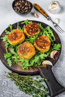 Veggie-patty-kotelett mit linsen, gemüse und rucola.