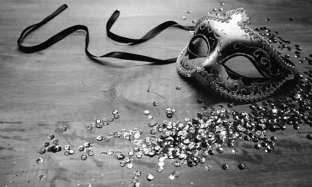 Venetianische karnevalsmaske mit pailletten auf hölzernem schreibtisch
