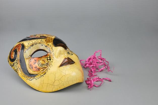 Venezianische karnevalsmaske lokalisiert auf einem grauen tisch