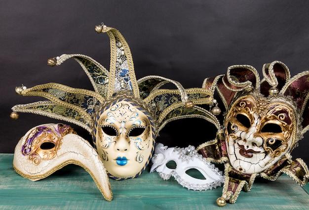 Venezianische karnevalsmasken auf grüner holzoberfläche gegen dunklen hintergrund