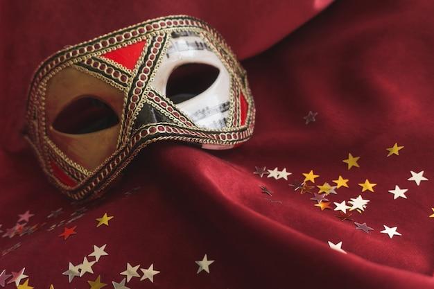 Venezianische maske auf einem roten stoff mit stern konfetti