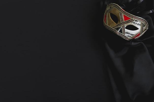 Venezianische maske für die augen auf einem schwarzen stoff