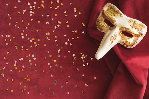 Venezianische maske mit einer großen nase auf einem roten stoff mit sternen konfetti nächsten