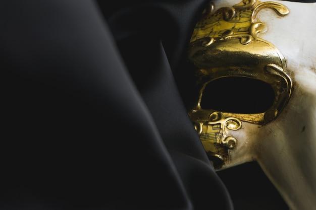 Venezianische maske mit einer langen nase auf einem schwarzen stoff nahe