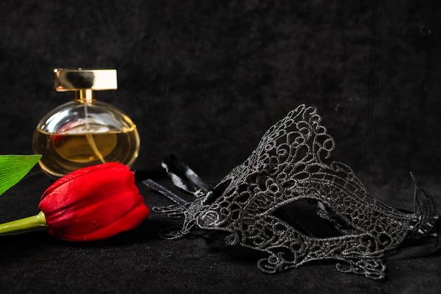 Venezianische maske mit roter tulpe und parfüm in einer dunklen, suggestiv beleuchteten umgebung. geheimnisvolles liebeskonzept, san valentin tag.