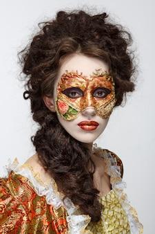 Venezianische maske. schöne frau im vintage-kleid und eine maske auf seinem gesicht.