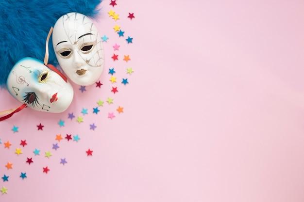 Venezianische masken in der nähe von federn und sternen